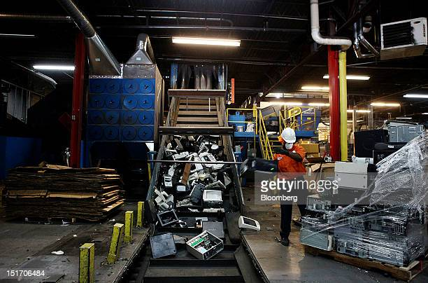 A worker tosses disassembled electronics onto a conveyor belt to get shredded at the WeRecycle Sanford erecycling plant in Mount Vernon New York US...