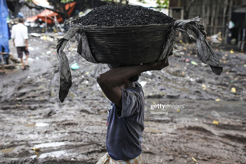 A worker transports a basket of coal on his head at a coal wholesale market in Mumbai, India, on Tuesday, July 2, 2013. India, the worlds third-largest coal consumer, imported 43 percent more of the fuel than a year ago on increased demand from power stations and steelmakers, according to shipping data, and is set to eclipse China as the top importer of power station coal by 2014. Photographer: Dhiraj Singh/Bloomberg via Getty Images
