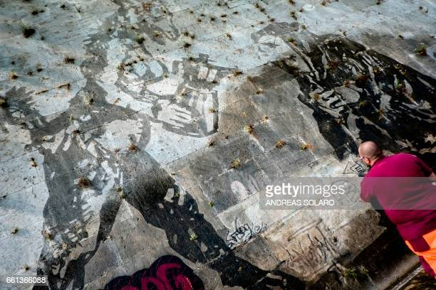 A worker tries cleans graffiti on the 'Triumphs and Laments' fresco which was completed along the banks of Romes Tiber river less than a year ago by...