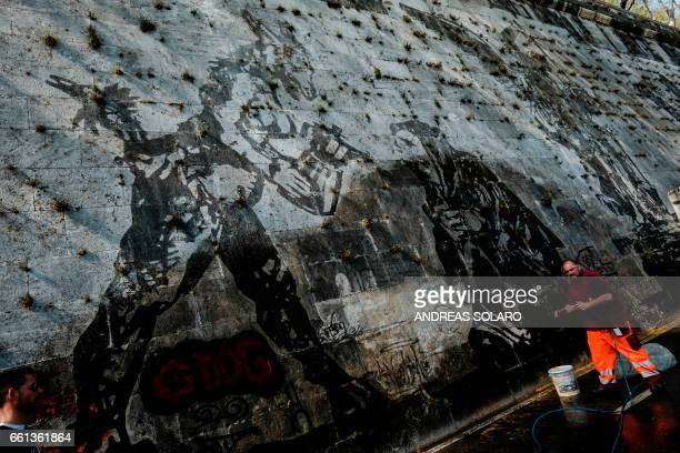 A worker tries to remove graffiti on the 'Triumphs and Laments' fresco which was completed along the banks of Romes Tiber river less than a year ago...