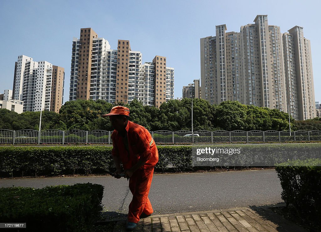 A worker trims hedges near residential buildings in Shanghai, China, on Sunday, June 30, 2013. China's President Xi Jinping said officials shouldn't be judged solely on their record in boosting gross domestic product, the latest signal that policy makers are prepared to tolerate slower economic expansion. Photographer: Tomohiro Ohsumi/Bloomberg via Getty Images