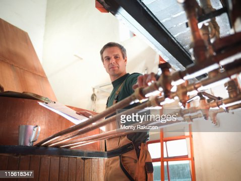 Worker turning taps at copper in brewery
