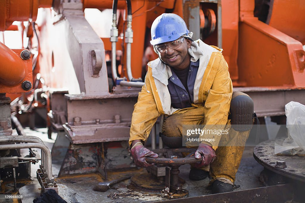 Worker turning wheel on oil rig