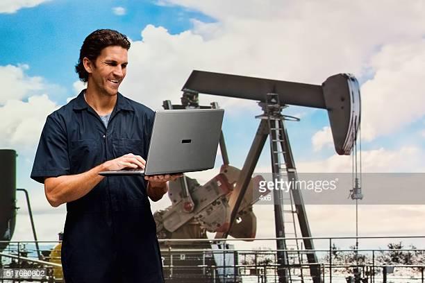従業員のタイプのノートパソコンで石油産業