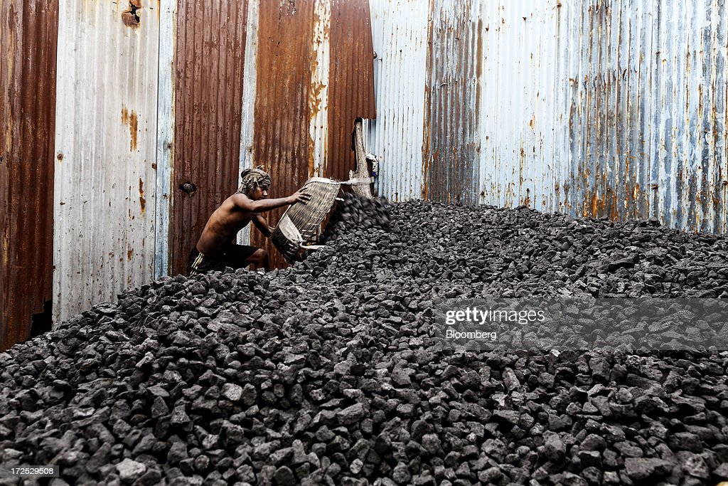A worker unloads a basket of coal onto a coal heap at a coal wholesale market in Mumbai, India, on Tuesday, July 2, 2013. India, the worlds third-largest coal consumer, imported 43 percent more of the fuel than a year ago on increased demand from power stations and steelmakers, according to shipping data, and is set to eclipse China as the top importer of power station coal by 2014. Photographer: Dhiraj Singh/Bloomberg via Getty Images
