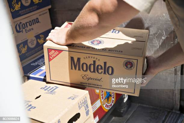 A worker unloads a case of Constellation Brands Inc Modelo beer from truck during a delivery outside a bar in Ottawa Illinois US on Tuesday June 27...