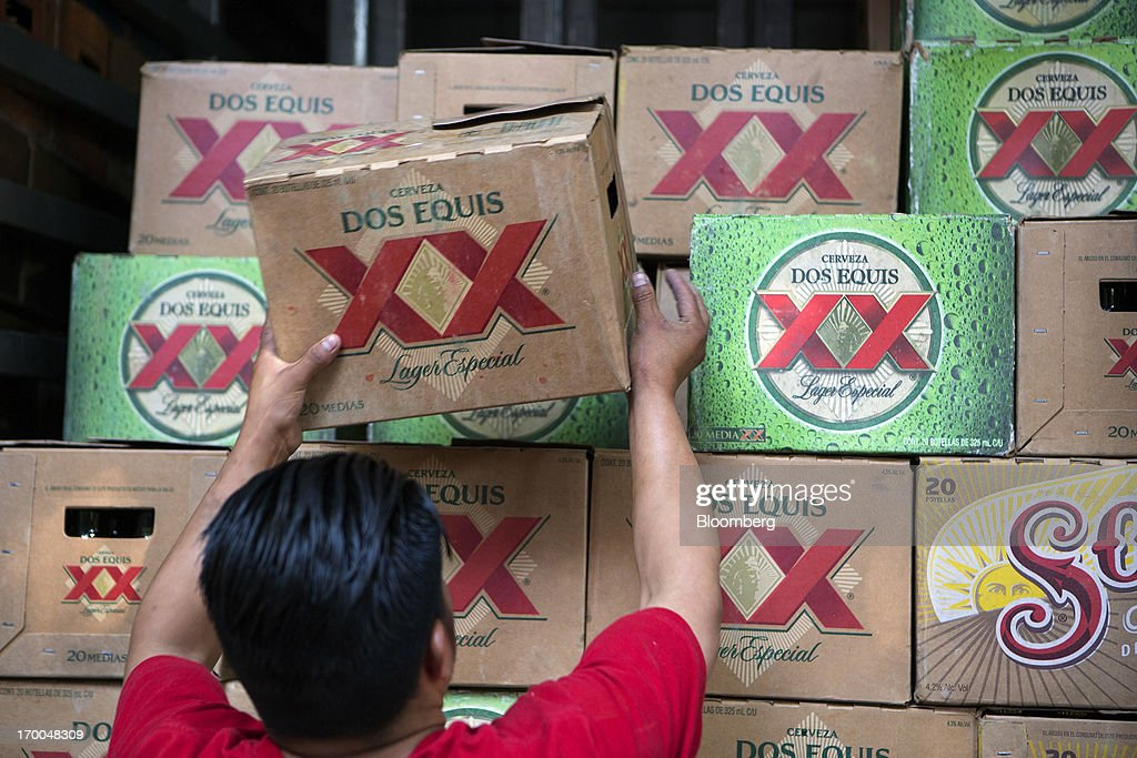 A worker unloads a case of Grupo Modelo SAB's Dos Equis brand beer from a truck operated by Cuauhtemoc-Moctezuma, a subsidiary of Heineken NV, while making deliveries in Mexico City, Mexico, on Thursday, June 6, 2013. Heineken NV and Grupo Modelo SAB, the dominant brewers in Mexico with brands such as Dos Equis and Corona, are nearing the end of an almost three-year-old government antitrust probe. Photographer: Susana Gonzalez/Bloomberg via Getty Images