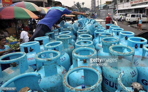 A worker unloads a delivery of liquefied petroleum gas at a market in Quezon City suburban Manila on February 5 2009 Philippine inflation rose 71...