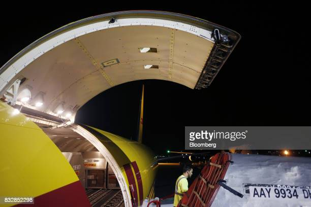 A worker unloads a DHL Worldwide Express cargo jet on the tarmac at the company's hub of Cincinnati/Northern Kentucky International Airport in Hebron...