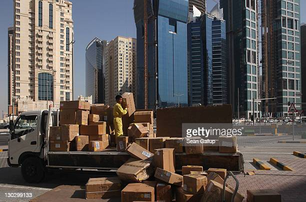 A worker unloads boxes during a delivery at a shopping mall among recentlybuilt skyscrapers in the budding new financial district on October 23 2011...