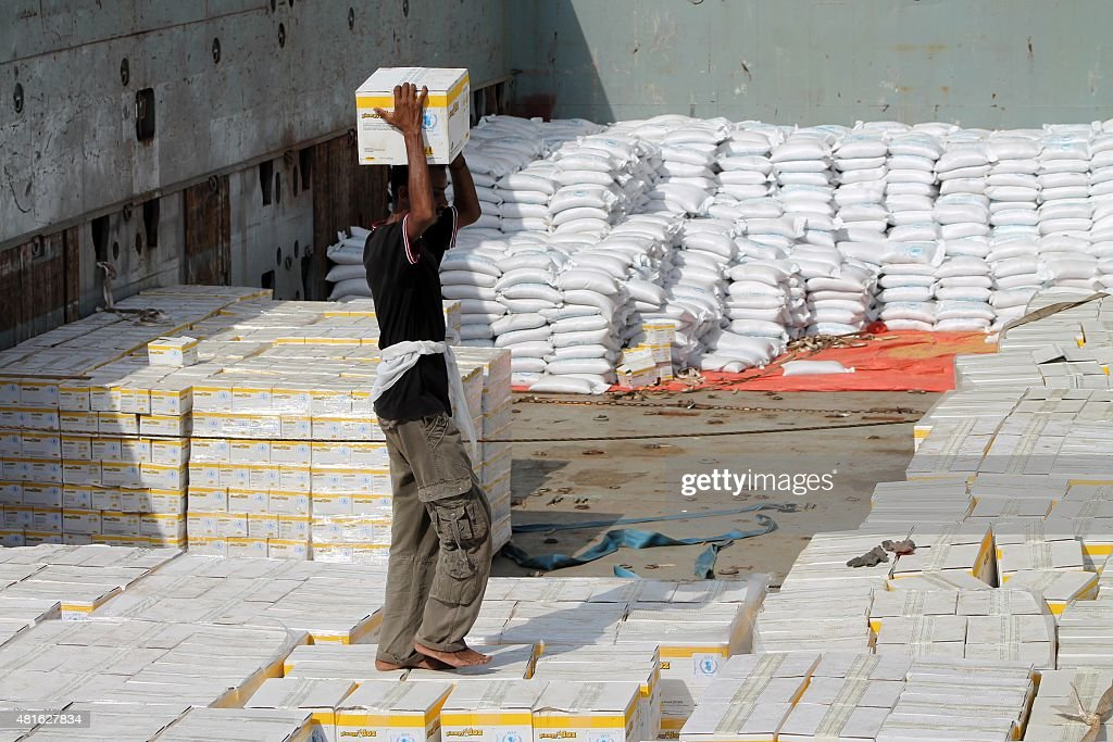 A worker unloads boxes from a UN's World Food Programme ship docked in Yemen's devastated port city of Aden on July 21 2015 as it brings in...