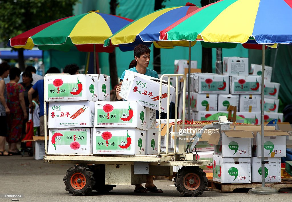 A worker unloads boxes of chili peppers at Samsan Agricultural Wholesale Market in Incheon, South Korea, on Friday, Aug. 16, 2013. South Korean producer prices declined 0.9 percent in July from a year earlier after a 1.4 percent drop in June, the central bank said in a statement today. Photographer: SeongJoon Cho/Bloomberg via Getty Images