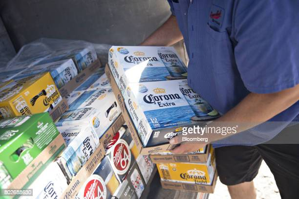 A worker unloads cases of Constellation Brands Inc Corona beer from truck during a delivery in Ottawa Illinois US on Tuesday June 27 2017...