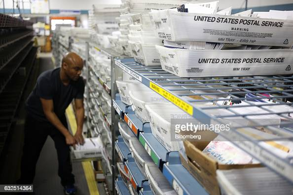 A worker unloads mail from an automated sorting machine at the United States Postal Service sorting center in Louisville Kentucky US on Friday Jan 13...