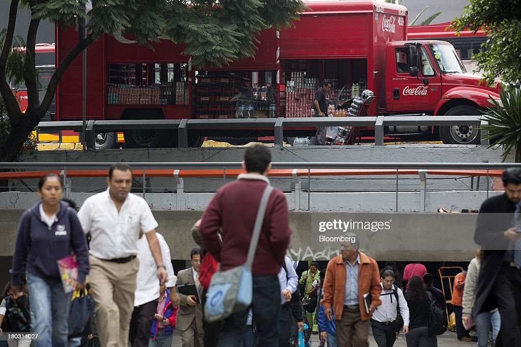 A worker unloads soft drinks for delivery from a Coca-Cola truck in Mexico city, Mexico on Tuesday, Sept. 10, 2013. Coca-Cola Femsa SAB, a bottler and distributor of Coca-Cola products in Mexico, agreed to buy Brazils Spaipa SA Industria Brasileira de Bebidas in a cash deal with a total transaction value of $1.86 billion. Photographer: Susana Gonzalez/Bloomberg via Getty Images