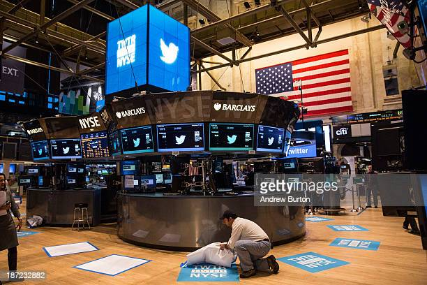 A worker unveils a floor mat bearing the logo of Twitter and the symbol on which Twitter's stock will traded on the floor of the New York Stock...