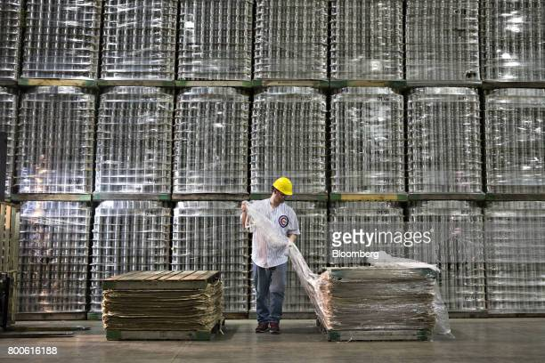 A worker unwraps packing materials in front of stacked pallets of canned vegetables at the Del Monte Foods Inc facility in Mendota Illinois US on...