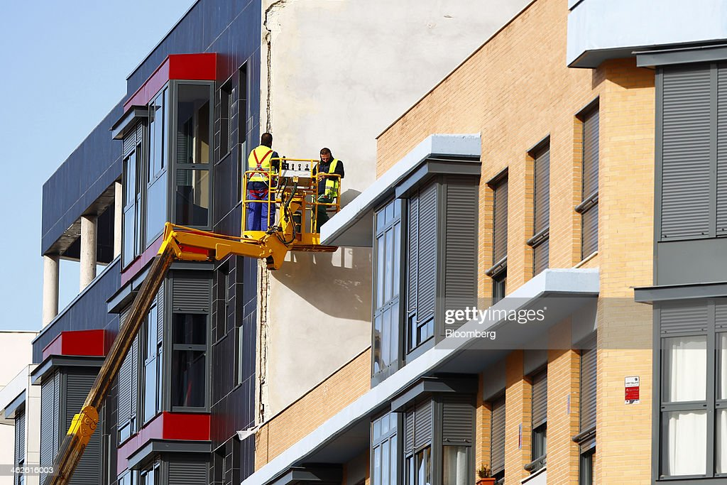 Worker use a cherry picker to fix a large crack in the rendering to a new residential building in Madrid, Spain, on Monday, Jan. 13, 2014. Spain's rental market is growing as government-spending cuts, a 26 percent jobless rate and subdued mortgage lending make home buying more difficult. Photographer: Angel Navarrete/Bloomberg via Getty Images