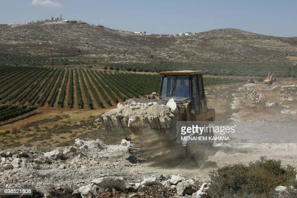 A worker uses a bulldozer to clear the land for the new Amichai settlement near the Shilo settlement between Ramallah and Nablus in the...