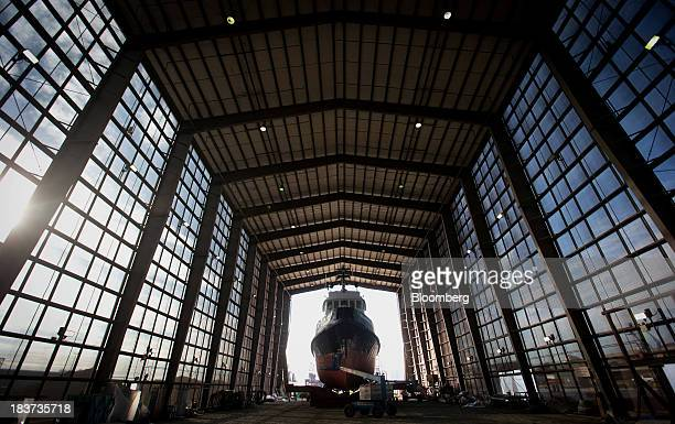 A worker uses a cherry picker to paint the Pacer tugboat as it undergoes repairs at the Seaspan Vancouver Shipyard in North Vancouver British...