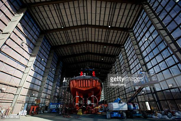 A worker uses a cherry picker while preparing to paint the Pacer tugboat as it undergoes repairs at the Seaspan Vancouver Shipyard in North Vancouver...