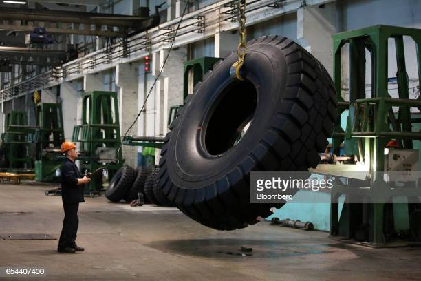 A worker uses a control unit to inspect a large 4000R57 sized tire in the control room at the Belshina JSC tire factory in Babruysk Belarus on...