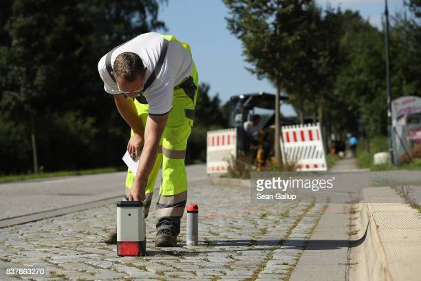 A worker uses a device to monitor the progress of a drill digging a horizontal hole in the ground below him during the installation of broadband...