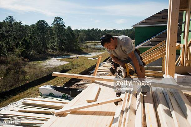 A worker uses a Dewalt circular saw during construction of a home in the Quail Woods subdivision in Wesley Chapel Florida US on Monday Jan 20 2014...
