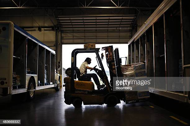 A worker uses a forklift to load a delivery truck with MillerCoors LLC alcoholic beverages at the Stagnaro Distributing Inc facility in Cincinnati...