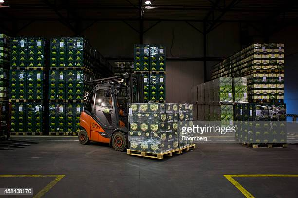 A worker uses a forklift truck to move a pallet of Staropramen beer boxes in the storeroom at the Pivovary Staropramen AS brewing company operated by...