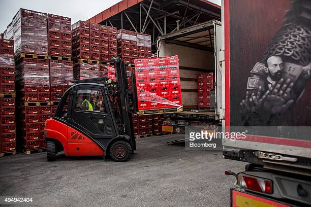 A worker uses a frontloader to fill the back of a truck with pallets of Budweiser Budvar beer for distribution at the Budejovicky Budvar NP...