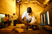 A worker uses a hammer and a letter punch to engrave gold bars with identifying marks at the Kibali gold mine operated by Randgold Resources Ltd in...