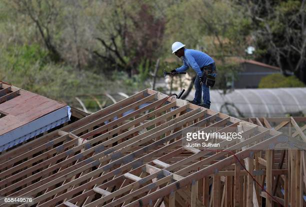 A worker uses a hammer as he builds a home at a housing development on March 27 2017 in Petaluma California According to a study by real estate...