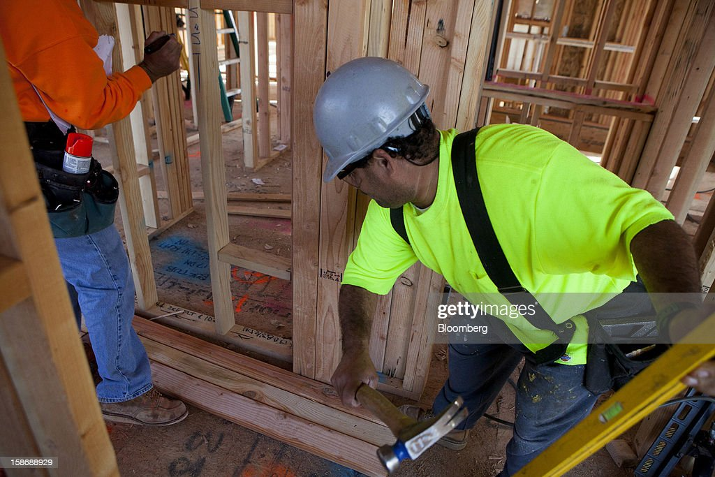 A worker uses a hammer to build a stud-framed wall inside a house under construction at Davidson Communities LLC's Arista at The Crosby development in Rancho Santa Fe, California, U.S., on Friday, Dec. 21, 2012. New home sales climbed to a 380,000 annual rate in November, the most since April 2010, according to the median forecast of 60 economists surveyed by Bloomberg before Dec. 27 figures from the Commerce Department. Photographer: Sam Hodgson/Bloomberg via Getty Images
