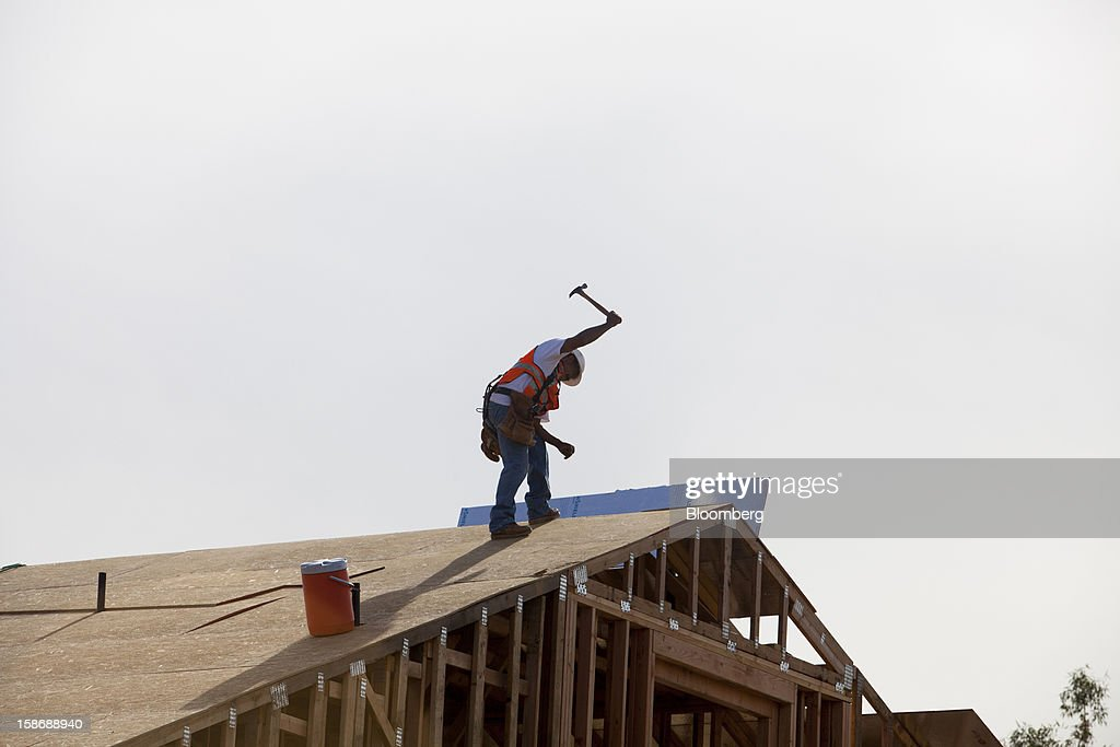 A worker uses a hammer to install roofing material on a house under construction at Davidson Communities LLC's Arista at The Crosby development in Rancho Santa Fe, California, U.S., on Friday, Dec. 21, 2012. New home sales climbed to a 380,000 annual rate in November, the most since April 2010, according to the median forecast of 60 economists surveyed by Bloomberg before Dec. 27 figures from the Commerce Department. Photographer: Sam Hodgson/Bloomberg via Getty Images