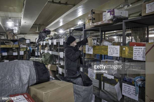 A worker uses a handheld scanner while sorting through packages at a ZTO Express Inc collection and distribution point in Shanghai China on Friday...
