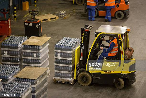 A worker uses a HysterYale Materials Handling Inc forklift truck to move a pallet of beer in the distribution center at the OAO Baltika brewery...