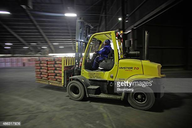 A worker uses a HysterYale Materials Handling Inc pallete truck to load bags of cement at the Hercules cement plant operated by PPC Ltd in Pretoria...