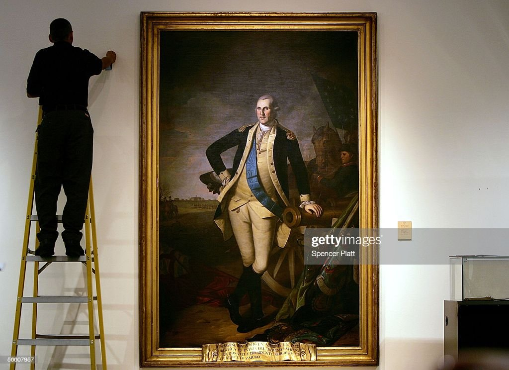 A worker uses a ladder to work near a full length portrait of former US President George Washington by Charles Wilson Peale at Christie's auction...