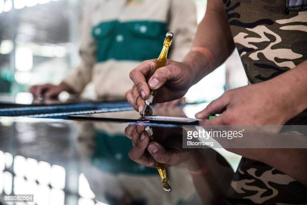 A worker uses a measuring tape while marking a sheet of glass at the Somvang Glass Factory on the outskirts of Vientiane Laos on Wednesday Nov 1 2017...