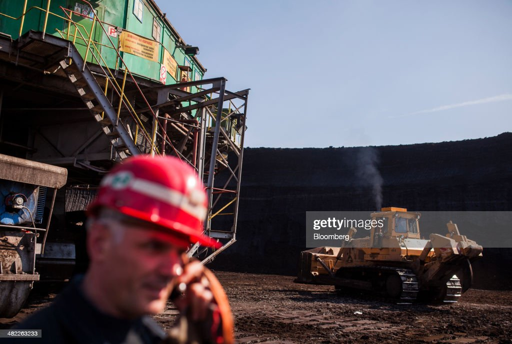 A worker uses a mobile handset beside a giant excavator during lignite, also known as brown coal, digging operations at the open pit mine operated by PGE Elektrownia Belchatow SA near Belchatow, Poland, on Wednesday, April 2, 2014. Polish power prices are set to stay above German contracts through 2015, reversing a historic discount, as the cost of keeping plants open in the eastern European nation is factored in, according to Vattenfall AB. Photographer: Bartek Sadowski/Bloomberg via Getty Images
