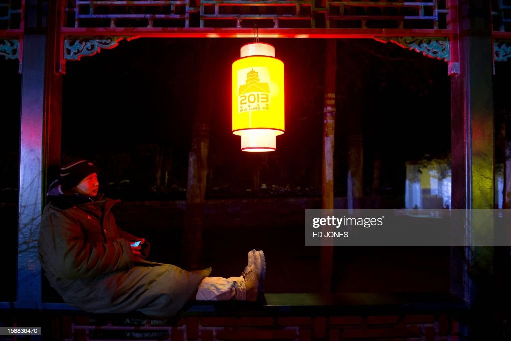 A worker uses a mobile phone as he rests beneath a lantern at the Summer Palace prior to a new year count-down event in Beijing on December 31, 2012. AFP PHOTO / Ed Jones