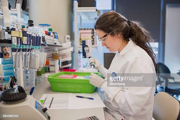 A worker uses a pipette in a lab at the Pfizer Inc research and development facility in Cambridge Massachusetts US on Monday Oct 26 2015 Pfizer is...