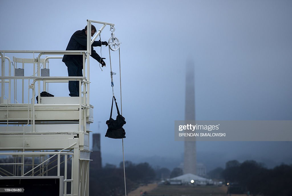 A worker uses a pulley to bring a bag to the top of a camera tower before an inauguration rehearsal on Capitol Hill January 13, 2013 in Washington, DC. President Barack Obama and Vice President Joe Biden will be ceremonially sworn in for a second four-year term during the 57th Inauguration on January 21. AFP PHOTO/Brendan SMIALOWSKI