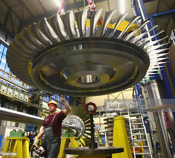 A worker uses a remote control to guide a rotor assembly for a turbine at the Siemens gas turbine factory on January 8 2010 in Berlin Germany Recent...