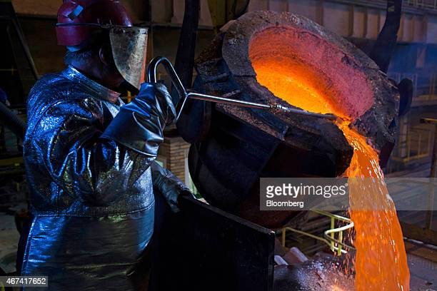 A worker uses a rod to control the flow of molten silver from a ladle before being cast at the KHGM Polska Miedz SA smelting plant in Glogow Poland...