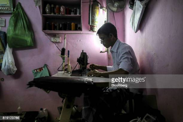 A worker uses a sewing machine while manufacturing a wallet at a leather workshop in the Dharavi area of Mumbai India on Tuesday July 18 2017 India's...