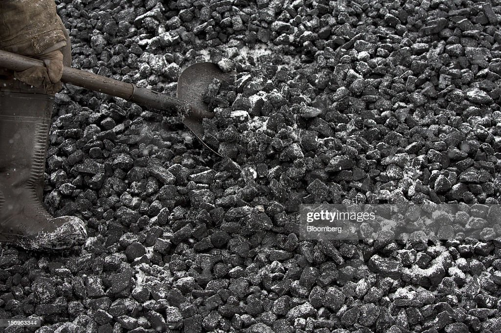 A worker uses a shovel to collect coal samples from a storage pile at the Sibirginsky open pit coal mine, owned by OAO Mechel and operated by Southern Kuzbass Coal Co., near Myski, in Kemerovo region of Siberia, Russia, on Friday, Nov. 23, 2012. OAO Mechel is Russia's biggest maker of steelmaking coal. Photographer: Andrey Rudakov/Bloomberg via Getty Images