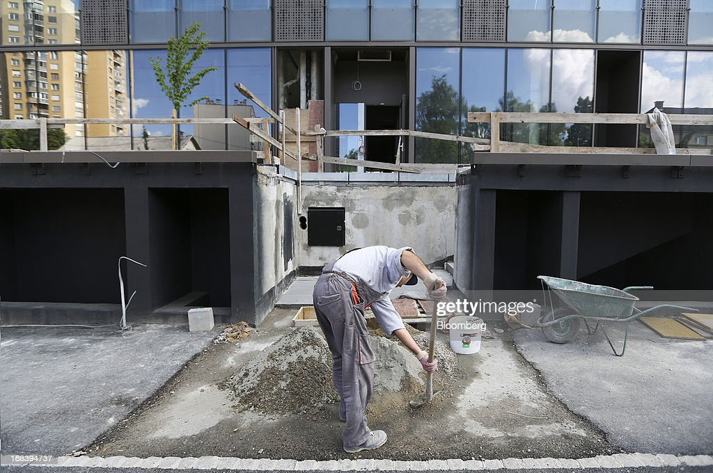 A worker uses a shovel to mix cement on a construction site for new residential apartments in Ljubljana, Slovenia, on Wednesday, May 8, 2013. Slovenia's recession will stretch into next year on weak domestic demand as the euro-area country teeters on the brink of needing an international bailout, the European Commission said. Photographer: Chris Ratcliffe/Bloomberg via Getty Images