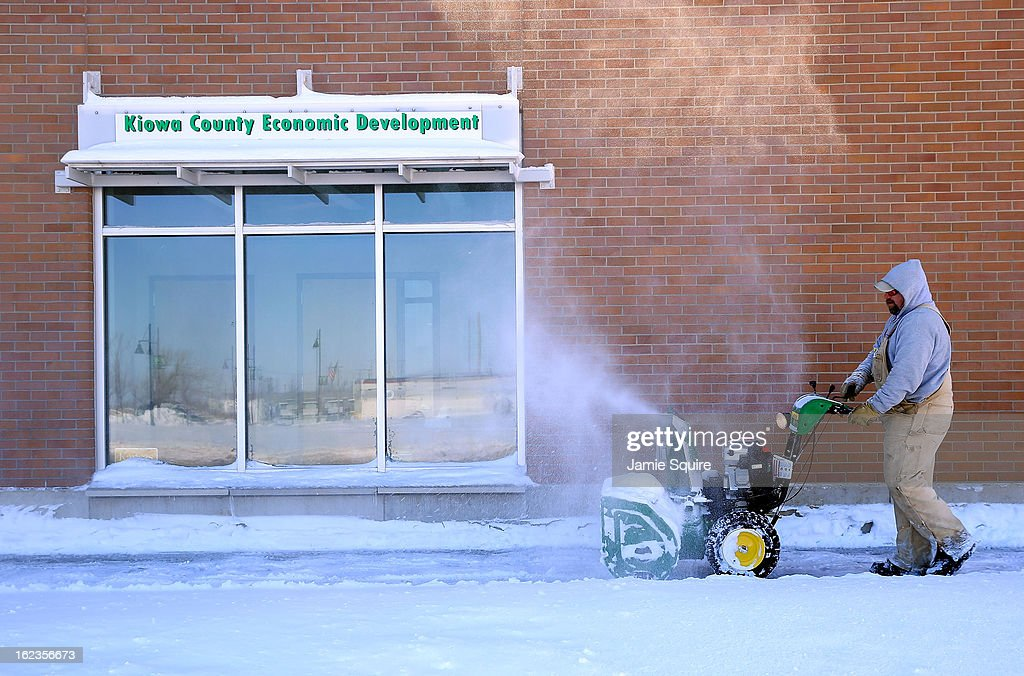 A worker uses a snowblower to clear a path after a large midwest winter storm on February 22, 2013 in Greensburg, Kansas. The storm dumped at least a foot of snow in Kansas and forcasters say it is headed to the northeast U.S.